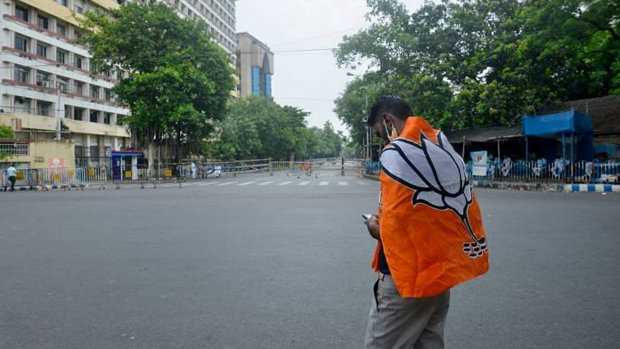 A BJP supporter wears the party flag during the election result day of the West Bengal Assembly election, in Kolkata Sunday | ANI