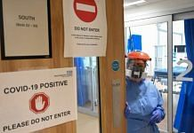 Representational image | A medical worker in PPE suit holds the door to a Covid-19 positive area, in the ICU at a hospital in Cambridge | Photo: Neil Hall | EPA via Bloomberg