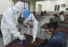 Health workers sanitize a patient receiving treatment at a Covid care centre in New Delhi