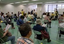 People wait to receive a dose of the Moderna vaccine at a newly-opened mass vaccination site in Tokyo, on 24 May 2021