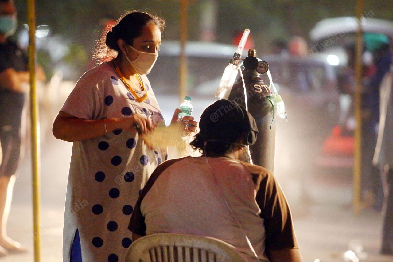A woman helps a relative attach her mask to an oxygen cylinder outside the Indirapuram Gurudwara  Praveen Jain   ThePrint