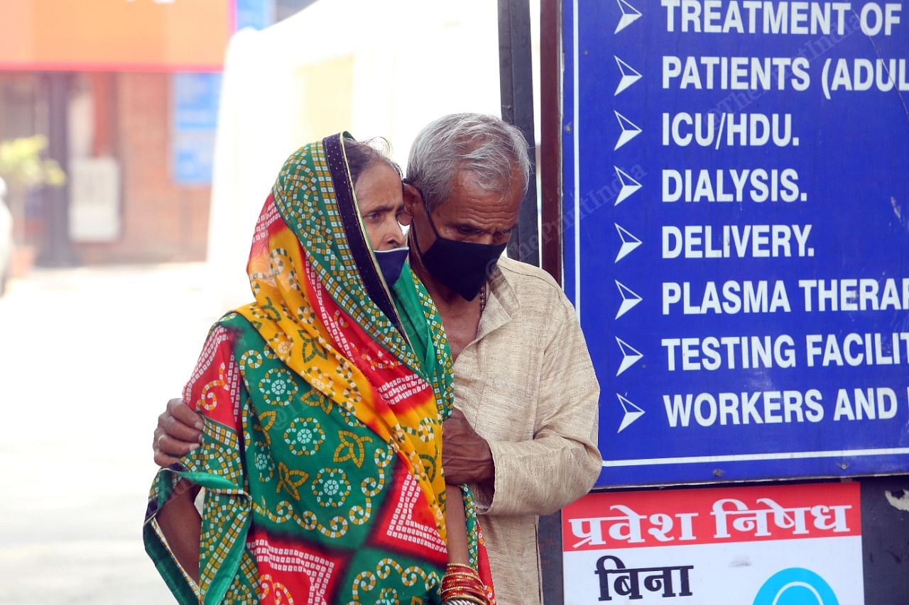 An old man holds his ailing wife outside LNJP   Praveen Jain   ThePrint