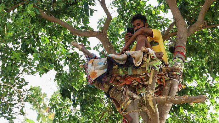 Shiva sits in his makeshift 'Covid isolation ward' — a mattress on a tree, in Nalagonda district, Telangana, in May 2021 | Manisha Mondal | ThePrint