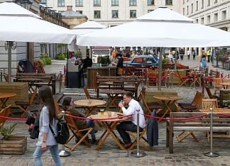 People sit at outdoor dining tables set up outside a restaurant at Covent Garden in London, on 11 May 2021