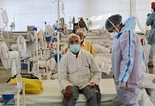 A health worker in PPE kit stand near Covid-19 patient, at Covid Care Center Rakabganj Gurudwara in New Delhi, on 25 May 2021   PTI