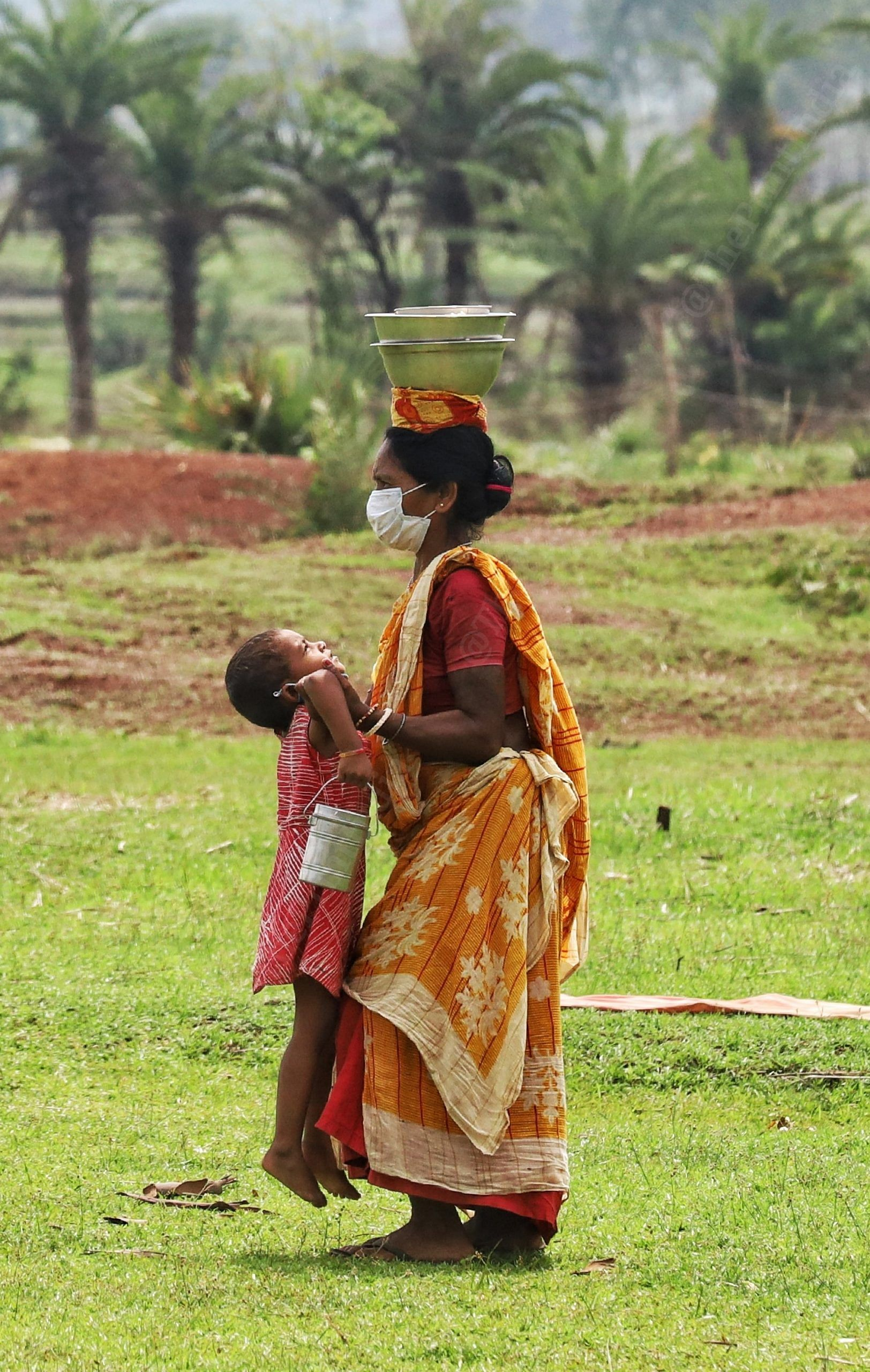 A woman carries the tiffin on her head and her daughter in her arms   Photo: Manisha Mondal   ThePrint