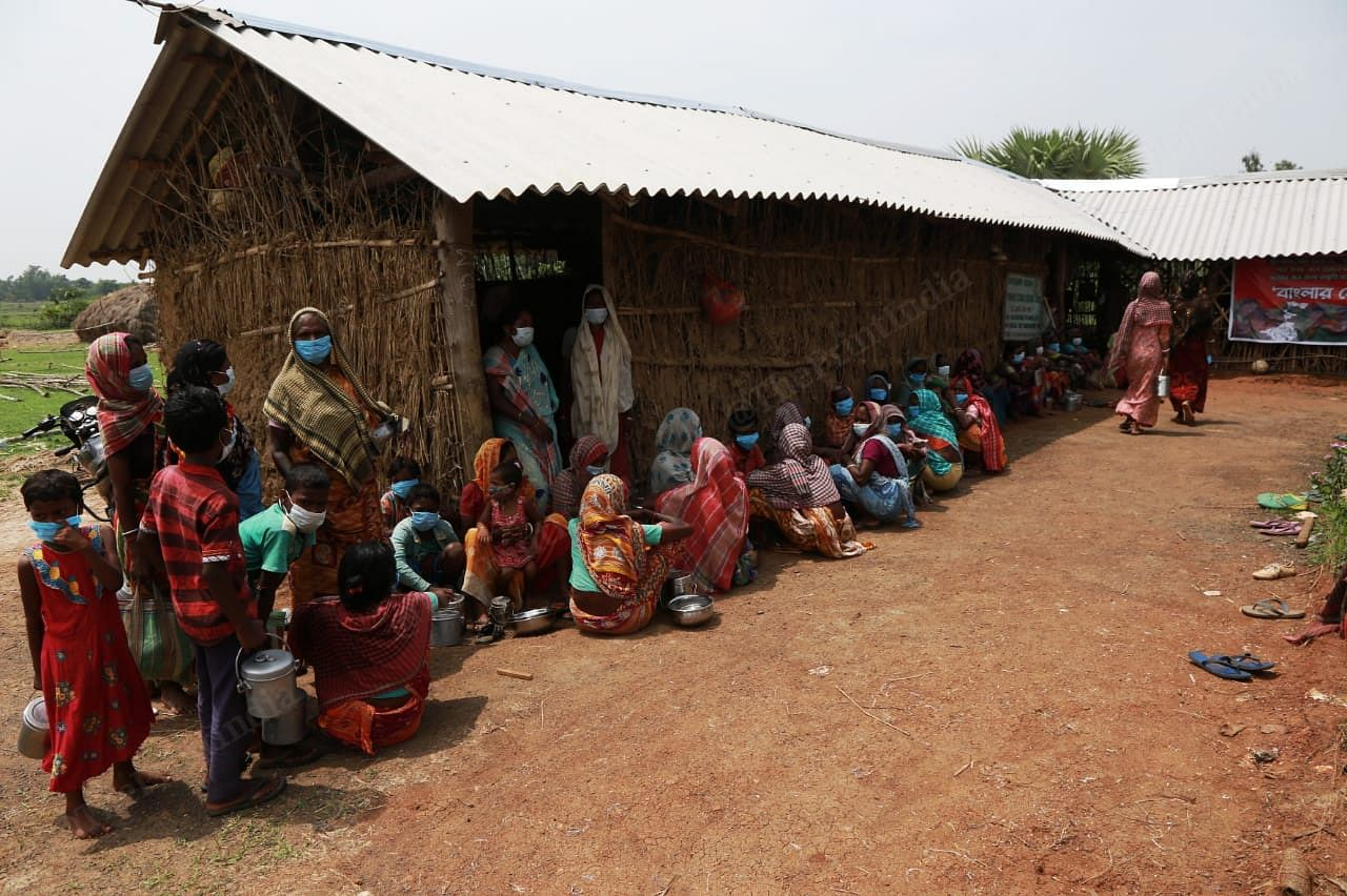 The country side has scorching sun as well as humidity. The women sit in the shade of the hut while waiting for food distribution   Photo: Manisha Mondal   ThePrint