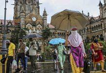 People wearing protective masks cross a road outside Chhatrapati Shivaji Maharaj Terminus (CST) railway station in Mumbai   Photographer: Dhiraj Singh   Bloomberg