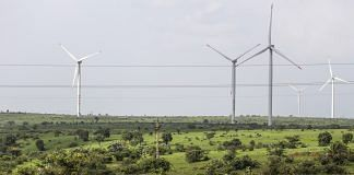 Wind turbines operating beyond electricity cables in Lahori, Madhya Pradesh, India  Photographer: Dhiraj Singh/Bloomberg