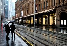 Pedestrians wearing protective masks stand along a near-deserted road during a lockdown in Sydney on 29 June 2021