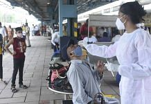A BMC health worker collects swab sample of a passenger for Covid testing, at Dadar railway station in Mumbai on 22 June 2021  PTI