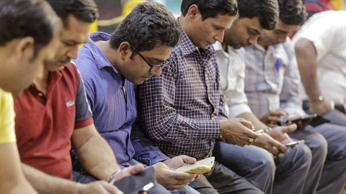 Representational image | People use smartphones at a railway station in Mumbai | Dhiraj Singh | Bloomberg