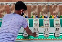 Rajiv Kumar, a worker at a sari unit in the West Champaran start-up zone, inspects a machine used to embroider the garment | Sajid Ali | ThePrint