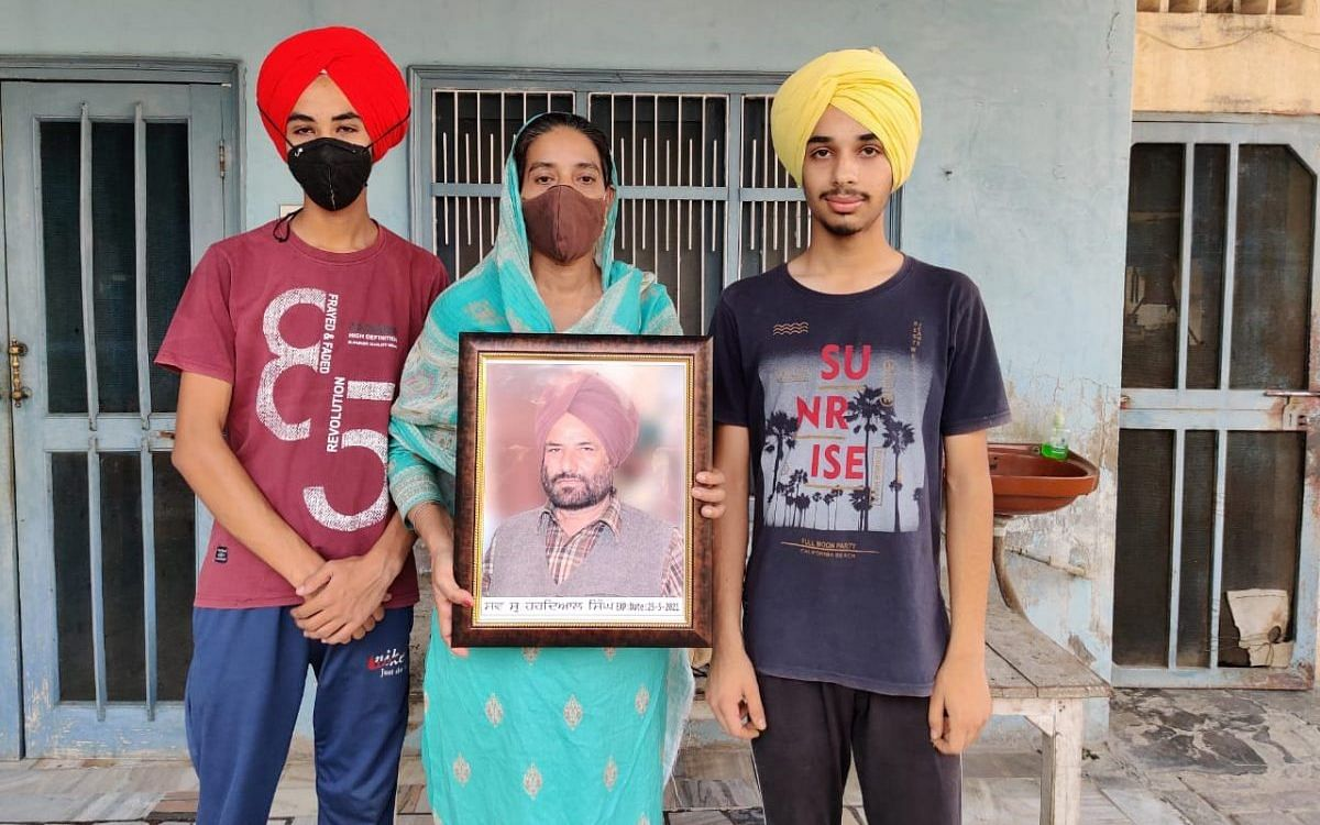 Singh's wife Kulwinder Kaur with their twin sons Damanpreet Singh (left) and Dilpreet Singh. Kaur holds a photograph of her husband | Photo: Reeti Agarwal/ThePrint