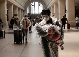 A man carrying a child, both wearing protective masks and raincoats, walk inside the Hankou railway station in Wuhan, Hubei Province, China, in April 2020 | Bloomberg