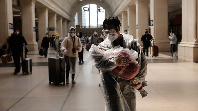 A man carrying a child, both wearing protective masks and raincoats, walk inside the Hankou railway station in Wuhan, China | Representational image | Bloomberg