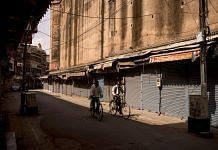 Cyclists ride past closed stores in a deserted market area during lockdown restrictions in Agra, on 6 June 2021   Bloomberg photo