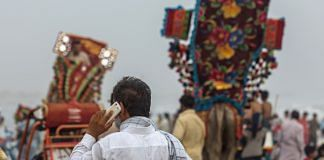 A man uses a mobile phone at Clifton Beach in Karachi