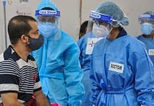 Health workers wearing PPE kits attend to Covid-19 patients at a newly set up temporary hospital at Tau Devi Lal Stadium in Gurugram, on 27 May 2021   PTI