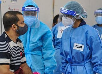 Health workers wearing PPE kits attend to Covid-19 patients at a newly set up temporary hospital at Tau Devi Lal Stadium in Gurugram, on 27 May 2021 | PTI