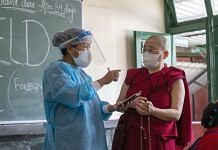 A health worker speaks with a Buddhist monk at a vaccination center set up at a Tibetan Children's Village School in Dharamshala, Himachal Pradesh | Photographer: Sumit Dayal | Bloomberg