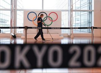 A worker sweeps in front of a banner for the Tokyo 2020 Olympic Games at Haneda Airport in Tokyo, Japan | Noriko Hayashi/Bloomberg