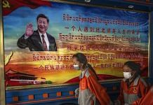 Tibetan students pass a poster showing Chinese President Xi Jinping in Lhasa, on 1 June 2021 | Photographer: Kevin Frayer/Getty Images AsiaPac via Bloomberg