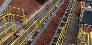 Workers monitor bauxite ore travelling a conveyor at the Vedanta Alumina Refinery in Lanjigarh district, Odisha