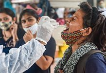 A health worker takes swab sample of a passenger for Covid-19 testing at Dadar railway station in Mumbai on 26 July 2021| PTI