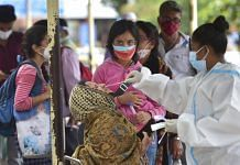 A health worker collects samples of passengers for Covid-19 test at city railway station during lockdown in Bengaluru on 24 July 2021| PTI