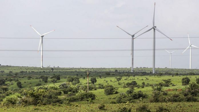 Wind turbines operating beyond electricity cables in Lahori, India  Photographer: Dhiraj Singh/Bloomberg