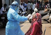 A medic collects swab from the mouth of a woman resident for Covid-19 test in a containment zone at Kurla, Mumbai Representational image | PTI