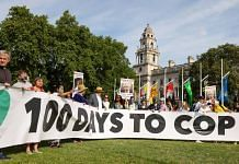 Protesters hold a banner reading '100 Days To Cop' during a demonstration marking 100 days until COP26 in London, on 23 July 2021 | Photographer: Hollie Adams | Bloomberg