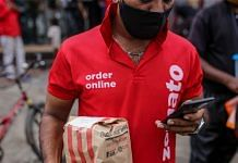 Zomato delivery rider looks at a smartphone while carrying an order in Mumbai   Representational image   Bloomberg