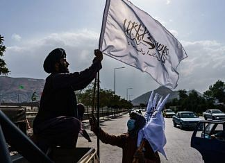 A boy selling Taliban flags brings his ware towards a military vehicle in Kabul on 20 August 2021 | Marcus Yam | Bloomberg via Getty Images