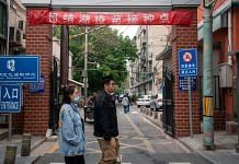 Pedestrians walk past a banner indicating a vaccination point at a residential compound in Beijing, China, in April 2021 | Yan Cong | Bloomberg