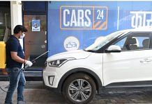 A Cars24 employee sanitises a used car   cars24.com