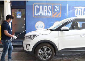 A Cars24 employee sanitises a used car | cars24.com