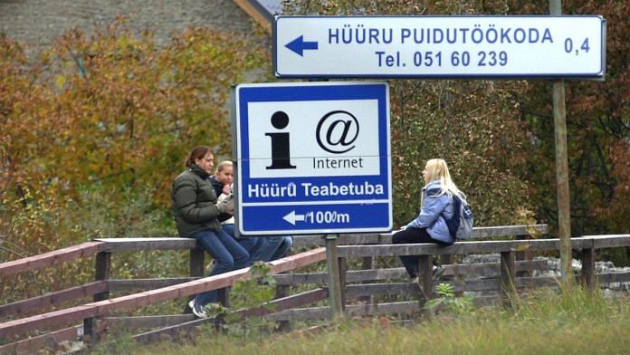 People sit close to a sign indicating internet availability, in Estonia's capital Tallinn