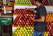A fruit vendor arranges produce at his store in Bengaluru, in June, 2021 | Dhiraj Singh | Bloomberg