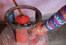 A woman connects an LPG cylinder to a stove at her home in Greater Noida   Photo: T. Narayan   Bloomberg