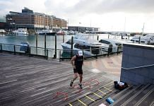 A man exercises at a deserted marina during a nationwide lockdown in Auckland, New Zealand in August 2021 | Brendon O'Hagan | Bloomberg