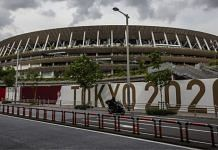 A man drives past the New National Stadium, the main stadium for the Tokyo Olympics in Tokyo   Photographer: Yuichi Yamazaki   Bloomberg