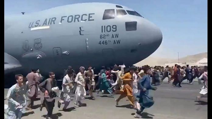 Afghanis scrambling to board the C-17 undercarriage of the US Air Force at the Kabul airport Monday | Twitter screengrab