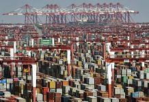 Shipping containers next to gantry cranes at the Yangshan Deepwater Port in Shanghai, China | Photographer: Qilai Shen | Bloomberg