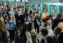 File photo of commuters wearing protective face masks while boarding and exiting a train at Saint-Lazare metro railway station in Paris, France. | Photographer: Cyril Marcilhacy | Bloomberg