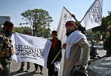 Taliban fighters hold Taliban flags while standing guard along a road in Kabul | Photographer: Wakil Kohsar/AFP/Getty Images via Bloomberg