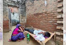 A mother sits by her child, suffering from viral fever, as he receives an intravenous drip at a quack's 'clinic' in Firozabad city | Shubhangi Misra | ThePrint