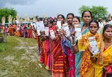 Beneficiaries show their Aadhaar Card as they wait in a queue to receive Covid-19 vaccine dose, at a government hospital in Nadia, West Bengal on 8 September 2021 | PTI