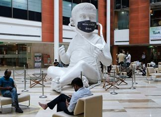 A protective mask adorns the sculpture of a baby with a stethoscope in the lobby at the Fortis Memorial Research Institute hospital in Gurgaon | Photographer: T. Narayan | Bloomberg